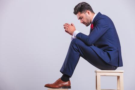 両手を一緒に見ているスタジオに座っているスーツの男の側の肖像 写真素材