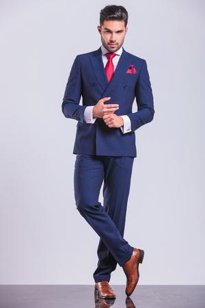 full body foto van hansome man in pak met gekruiste benen, terwijl het aanraken van de handen Stockfoto