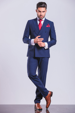 full body picture of hansome man in suit with legs crossed while touching hands Standard-Bild