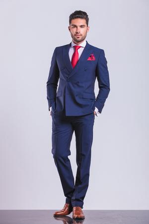 elegante man poseren volledige lichaam op studio achtergrond met handen in de zakken