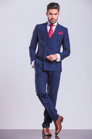 piernas hombre: Retrato de cuerpo completo del hombre de negocios guapo posando de pie piernas cruzadas con la mano en el bolsillo