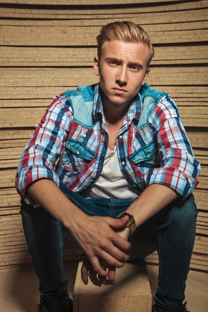 young guy: serious young male sitting on a box in wooden studio background while touching hands and looking at the camera
