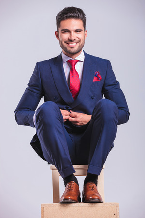 hansome: hansome business man sitting on a chair while unbuttoning his jacket