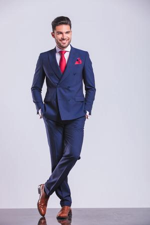 足とポーズ スーツを着た若い男がポケットに手を持ちながら交差