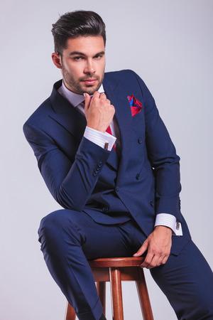 彼のあごに触れる中で、スタジオに座っているエレガントなスーツを着た事業男