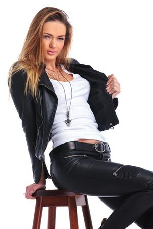 mujeres sentadas: Mujer joven atractiva que presenta en estudio la organización de su chaqueta de cuero mientras se está sentado en la silla Foto de archivo