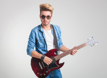 cool guy: cool blonde guy playing electric guitar while posing for the camera in studio background Stock Photo