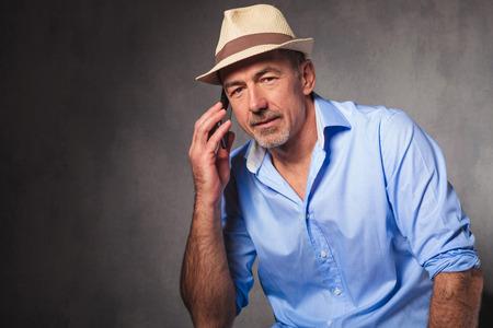 hombres maduros: hombre pose en el fondo del estudio que lleva un sombrero mientras se habla por el teléfono y mirando a la cámara