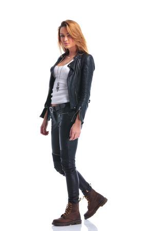 americana: Actitud modelo atractiva linda en la chaqueta de cuero mientras se camina en el estudio y mirando a la cámara Foto de archivo