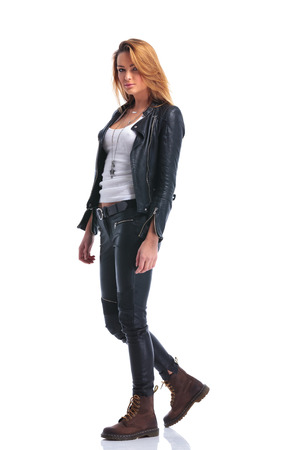 cute model pose in leather jacket while walking in studio and looking at the camera