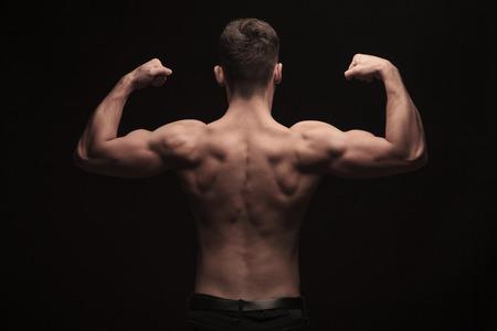 topless: vue arri�re du torse nu homme muscl� posant en fond sombre studio tout en fl�chissant Banque d'images