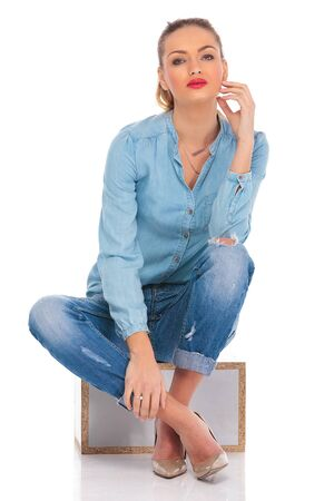girl legs: young girl posing seated in studio on a box with legs crossed while touching face