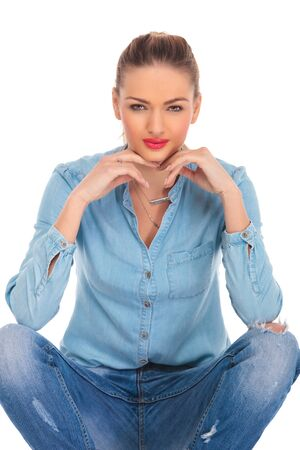 blue shirt: portrait of beautiful girl seated in studio background with hands on her knees while touching her face