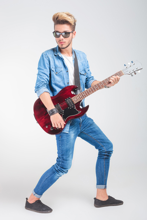 looking away from camera: artist playing guitar in studio background while posing looking away from the camera
