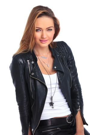jacket: retrato de la hermosa mujer joven que presenta en chaqueta de cuero sonriendo mientras mira a la cámara Foto de archivo