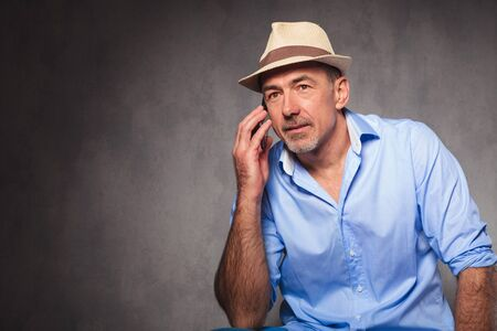 hombre sentado: retrato de hombre sentado y posando para la cámara mientras se mira lejos y habla en el teléfono Foto de archivo