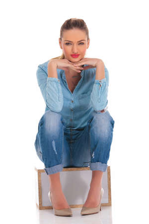 girl sit: beautiful caucasian woman in denim pose seated with hands on knees touching face while looking at the camera