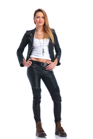 スタジオ背景腰に触れると、カメラ目線でポーズをとってレザー ジャケットとブーツでセクシーなブロンドの女の子
