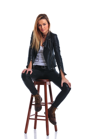 hot pants: girl dressed in boots and leather jacket pose seated in white studio background while looking at the camera