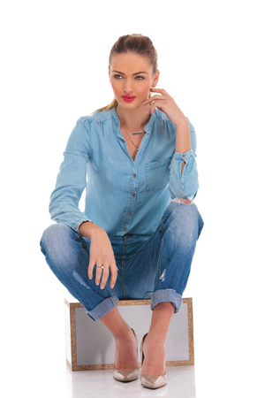 looking away from camera: blonde model in denim pose seated in studio background with hand on knee touching face while looking away from the camera