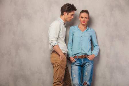 looking away from camera: casual couple pose in studio background with hands in pockets, man stares away while the girl is looking at the camera