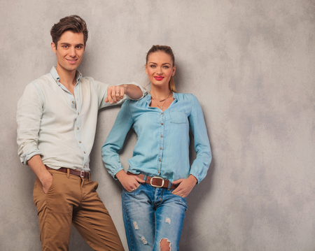 lean on hands: handsome man lean on his girl shoulder while she poses with hands in pockets in studio background