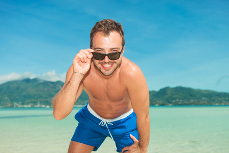 briefs: smiling young man on the beach posing in his briefs while fixing his sunglasses Stock Photo
