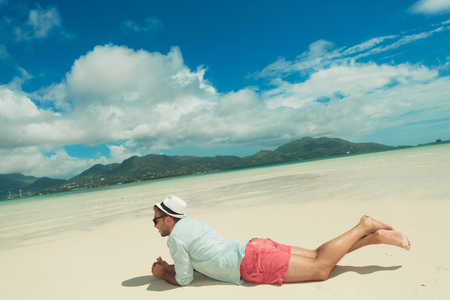man lying down: young man lying down in sand contemplating the exotic view Stock Photo