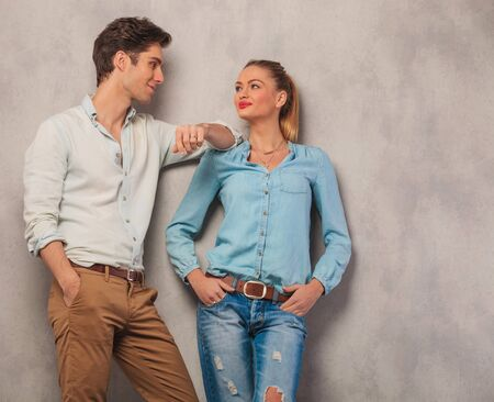 lean on hands: attractive man with hand in pocket lean on girl shoulder while she looks at him with hands in pockets in studio background Stock Photo