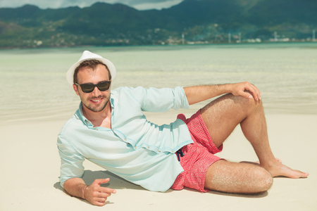 hansome: portrait of smiling hansome man lying on the beach while wearing shirt, pants, hat and sunglasses