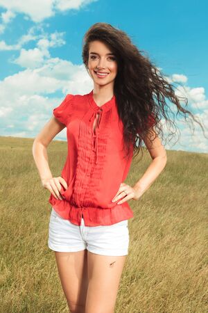wind blowing: beautiful brunette women posing with her hands on her waist while wind blowing through her hair