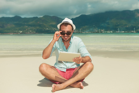 beach front: young man on the beach smiling and fixing his sunglasses while holding ipad
