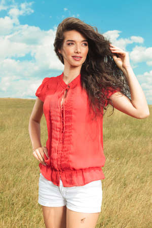 blue sky and fields: beautiful woman wearing red blouse and white shorts, touching her hair while looking away off the camera Stock Photo