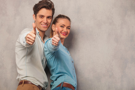 okay sign: young man with his girlfriend posing in studio background while showing thumbs up sign Stock Photo