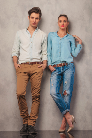 man shirt: casual couple standing in studio leaning on the wall while posing with hands in pockets