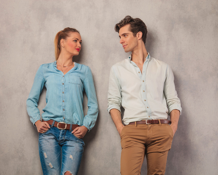 young couple looking at each other with hands in pockets in studio background