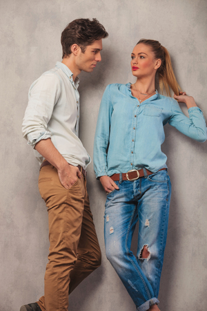 hair man: portrait of man with hands in pockets looking at his girfriend posing in studio while arranging her hair