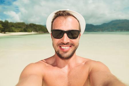 hombre con sombrero: hombre joven atractivo que toma una autofoto en la playa mientras se usan tonos y un sombrero blanco