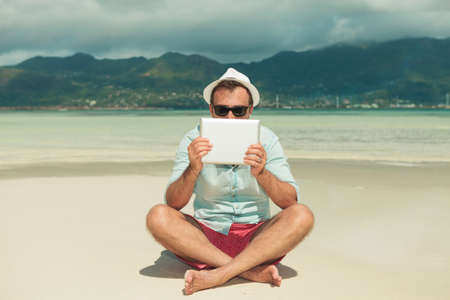 beach front: handsome man wearing sunglasses hiding behind tablet while sitting legs crossed on the beach