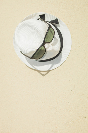 ocean background: white hat with black strap and black sunglasses placed on the beach