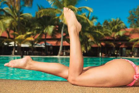 mujer atractiva en bikini rosa con las piernas en el aire cerca de la piscina en lugar exótico