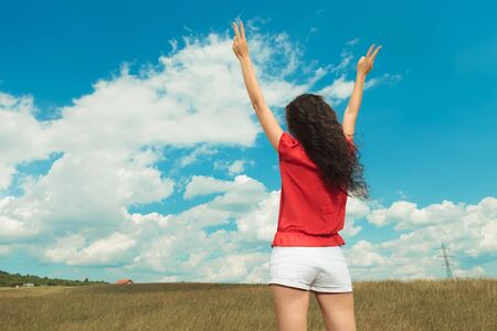 back view of a woman dressed in white shorts with red blouse showing victory sign with both hands while standing in the fields photo