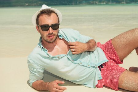sun down: handsome man lying down the beach with white hat and sunglasses on while opening his shirt