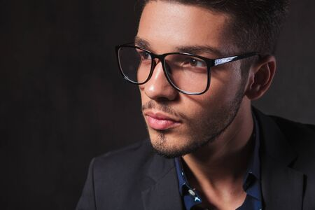 inteligent: portrait of smart man wearing glasses in dark studio background while looking away from the camera