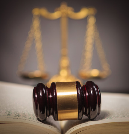 fair trial: judges hammer in the middle of a law book in front of a golden scale , fair law and justice concept