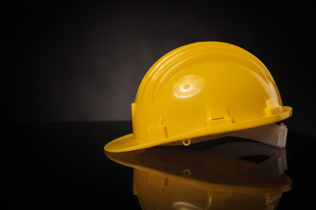 safety wear: side view of a yellow construction safety  helmet on a black table with reflexion
