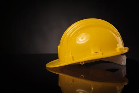 zijaanzicht van een gele bouw helm op een zwarte tafel met reflectie Stockfoto