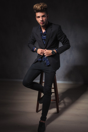 fashion model: portrait of attractive elegant guy posing seated in dark studio background while fixing his jacket