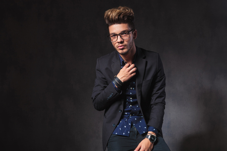 he: portrait of skinny guy fixing his shirt while seated. he is wearing glasses in dark studio background. Stock Photo