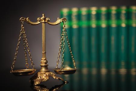 Concept de droit et de justice, échelle d'or antique devant une rangée de livres de droit en studio